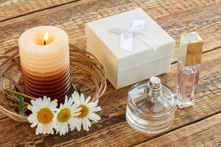 Bouquet of chamomiles, perfumes, burning candle and white gift box on wooden boards. Top view. Holiday concept.