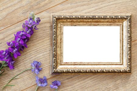 Vintage photo frame with copy space and blue flowers on old wooden boards.
