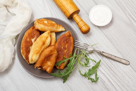 Plate with fried pies, greens, fork and wooden rolling pin, bowl with sour cream on wooden table. Top view.