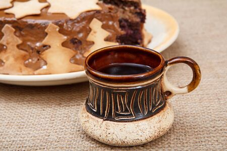 Homemade chocolate cake decorated with ornament and clay cup of black coffee on the sackcloth. Imagens
