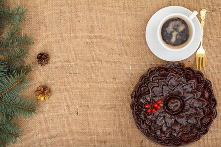 Chocolate cake decorated with bunch of viburnum, cup of coffee with branch of spruce on table with branch of spruce and sackcloth. Top view. Merry Christmas concept.