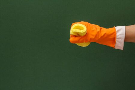 Womans hand in orange protective glove with yellow sponge in a green background. Washing and cleaning concept.