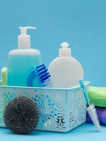 Plastic basket with bottles of dishwashing liquid, glass and tile cleaner, brushes on blue background. Washing and cleaning products. 写真素材