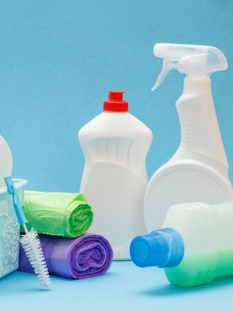 Bottles of dishwashing liquid, glass and tile cleaner, brush and garbage bags on blue background. Washing and cleaning products.