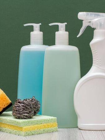 Plastic bottles of detergent for microwave ovens and stoves, glass and tile cleaner and sponges with green background. Washing and cleaning products. 写真素材