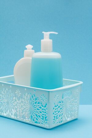 Plastic basket with bottles of dishwashing liquid, glass and tile cleaner on blue background. Washing and cleaning products.