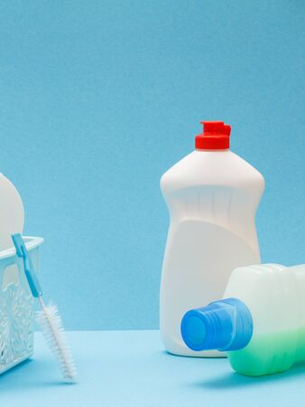 Plastic bottles of dishwashing liquid, glass and tile cleaner, brushes on blue background. Washing and cleaning products.