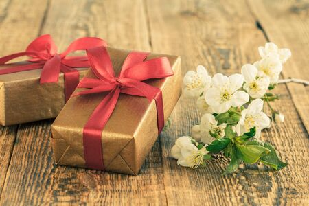Gift boxes wrapped with red ribbon on wooden boards decorated with flowers of jasmine. Color tone changed. Stock Photo