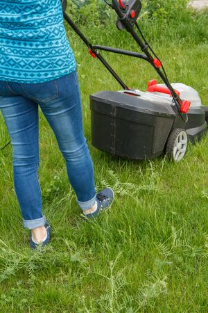 Female gardener is operating with lawn mower in the garden in spring day. Mower grass equipment. Mowing gardener care work tool.