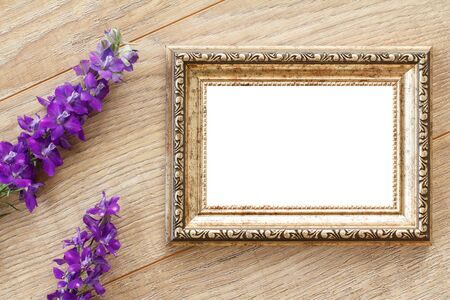 Vintage photo frame with copy space and blue flowers on wooden boards. Top view.