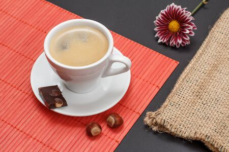 Cup of coffee on saucer with piece of chocolate bar, nuts on bamboo napkin, sackcloth bag and flower bud on a black background. Top view.