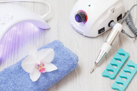Milling cutter, turned on led UV lamp, toe separators and a towel with orchid on gray wooden background. A set of cosmetic tools for professional hardware manicure. Top view