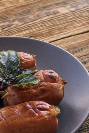 Close-up view of grilled sausages with basil leaves on plate and wooden boards. Top view.