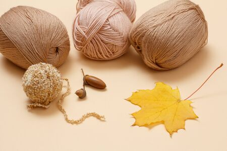 Knitting yarn balls and dry maple leaf on a beige background. Knitting concept. Top view. 版權商用圖片