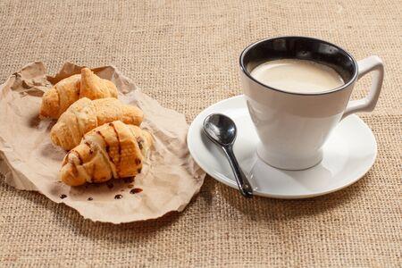 Tasse schwarzen Kaffee mit Löffel auf Untertasse, frische Croissants mit Schokolade auf Packpapier mit Sackleinen im Hintergrund. Standard-Bild