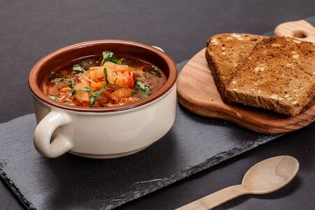 Ukrainian traditional borsch in porcelain bowl with rye bread on stone board. Top view.