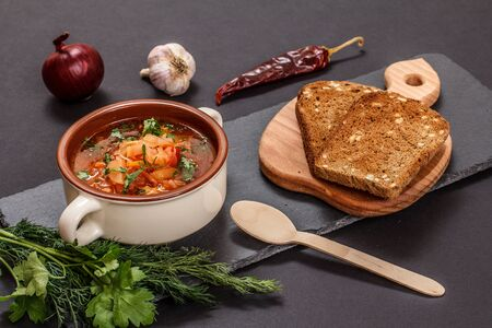 Ukrainian traditional borsch in porcelain bowl with rye bread, parsley, onion, garlic and chilli pepper on stone board. Top view.