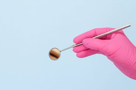 Dentist's hand in a pink latex glove with mouth mirror on blue background. Medical tools concept.