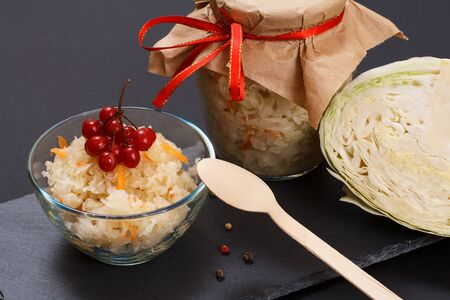 Homemade fermented cabbage with carrot and cluster of viburnum in glass bowl. Fresh head of cabbage and glass can on the background. Vegan salad. Dish is rich in vitamin U. Food great for good health. Banco de Imagens