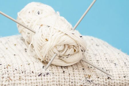 White pullover and skein of yarn with metal knitting needles on a blue