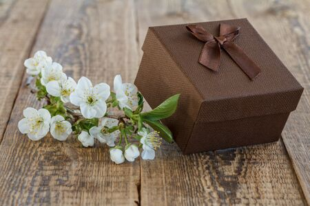 Brown gift box decorated with flowers of jasmine on old wooden boards.