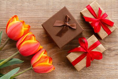 Gift boxes with red tulips on wooden boards. Greeting card concept. Top view.