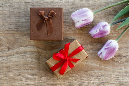 Gift boxes with red ribbons and beautiful tulips on the wooden boards. Top view. Concept of giving a gift on holidays.