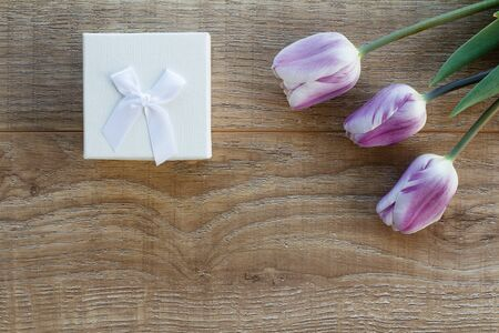 White gift box and beautiful tulips on the wooden boards. Top view. Concept of giving a gift on holidays.