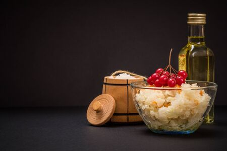 Homemade fermented cabbage in glass bowl in black background. Salt and bottle of oil on the background.. Vegan salad. Dish is rich in vitamin U. Food great for good health.