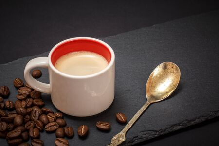 Cup of coffee, coffee beans and metal spoon on black background. Top view.