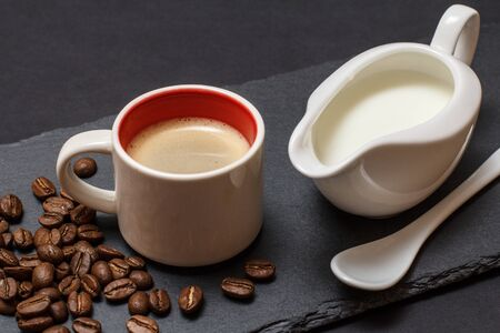 Cup of coffee, coffee beans, spoon and jug of cream on black background. Top view.