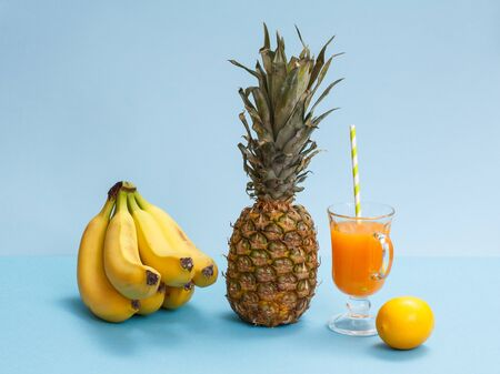 Natural composition from tropical fruits. Bananas, fresh pineapple and lemon with glass of fruit juice on blue background.