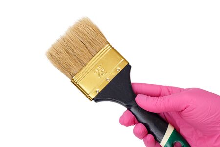 Female hand in a pink latex glove holding a house painter brush on a white isolated background. Repair tool. Building tool. Close-up view.