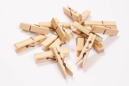 Heap of wooden clothes pins on white background. Top view. 版權商用圖片