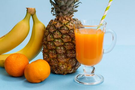 Glass of fruit juice, fresh pineapple and mandarins on blue background.