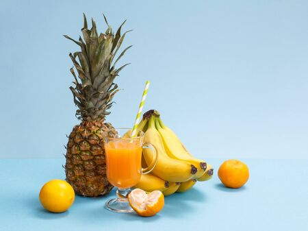 Natural composition from tropical fruits. Fresh pineapple, bananas, tangerines and lemon with glass of fruit juice on blue background.