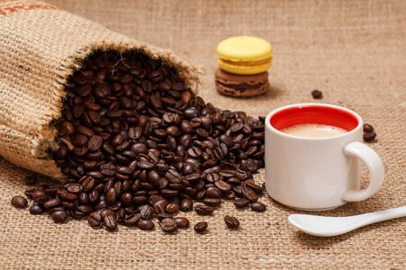 Cup of coffee, macaroons and roasted coffee beans in a canvas sack on sackcloth.