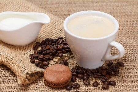 Cup of cappuccino, sauceboat with cream, coffee beans, canvas sack and macaroons on sackcloth background. Top view.