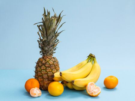 Natural composition from tropical fruits. Fresh pineapple, bananas, lemon and tangerines on blue background.