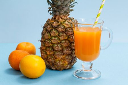 Glass of fruit juice, fresh pineapple, lemon and mandarin on blue background.