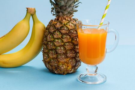 Glass of fruit juice, fresh pineapple and bananas on blue background.