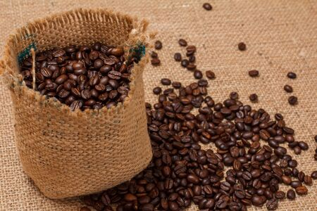 Roasted coffee beans in a canvas sack on sackcloth background. Top view. Zdjęcie Seryjne