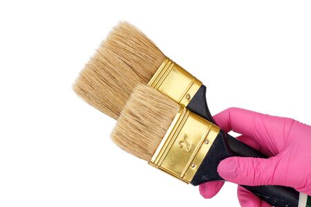 Female hand in a pink latex glove holding a house painter brushes on a white isolated background. Repair tool. Building tool. Close-up view. Zdjęcie Seryjne