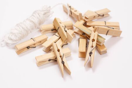 Heap of wooden clothes pins and clothesline on white background. Top view.