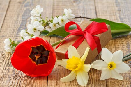 Flowers of tulip, daffodils and jasmine with gift box on old wooden boards.