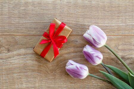 Gift box with red ribbons and beautiful lilac tulips on the wooden boards. Top view. Concept of giving a gift on holidays.