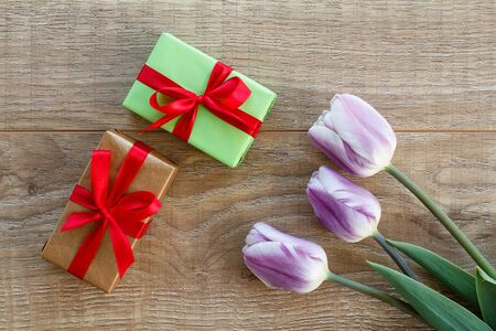Gift boxes with red ribbons and beautiful lilac tulips on the wooden boards. Top view. Concept of giving a gift on holidays. Zdjęcie Seryjne