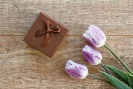 Brown gift box with beautiful lilac tulips on the wooden boards. Top view. Concept of giving a gift on holidays.