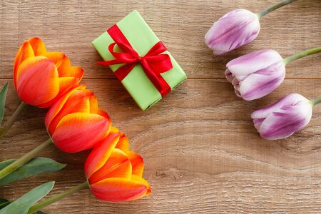 Gift box with red and lilac tulips on wooden boards. Greeting card concept. Top view.
