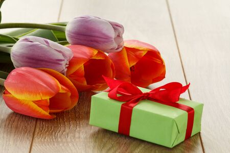 Gift box with red and lilac tulips on wooden boards. Greeting card concept. Banco de Imagens